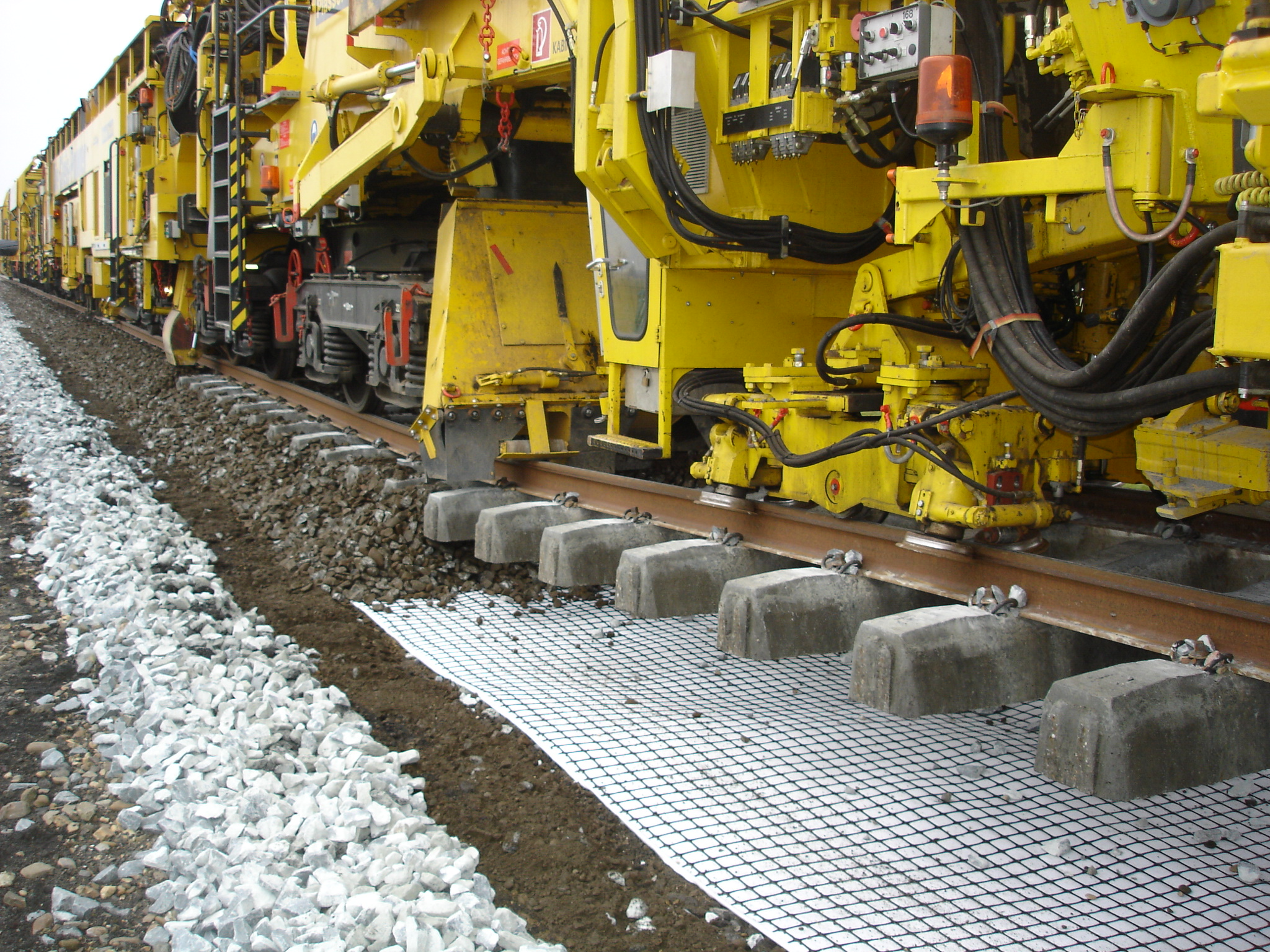 Trackbed geocomposite installed below rail ballast using automated undercutter